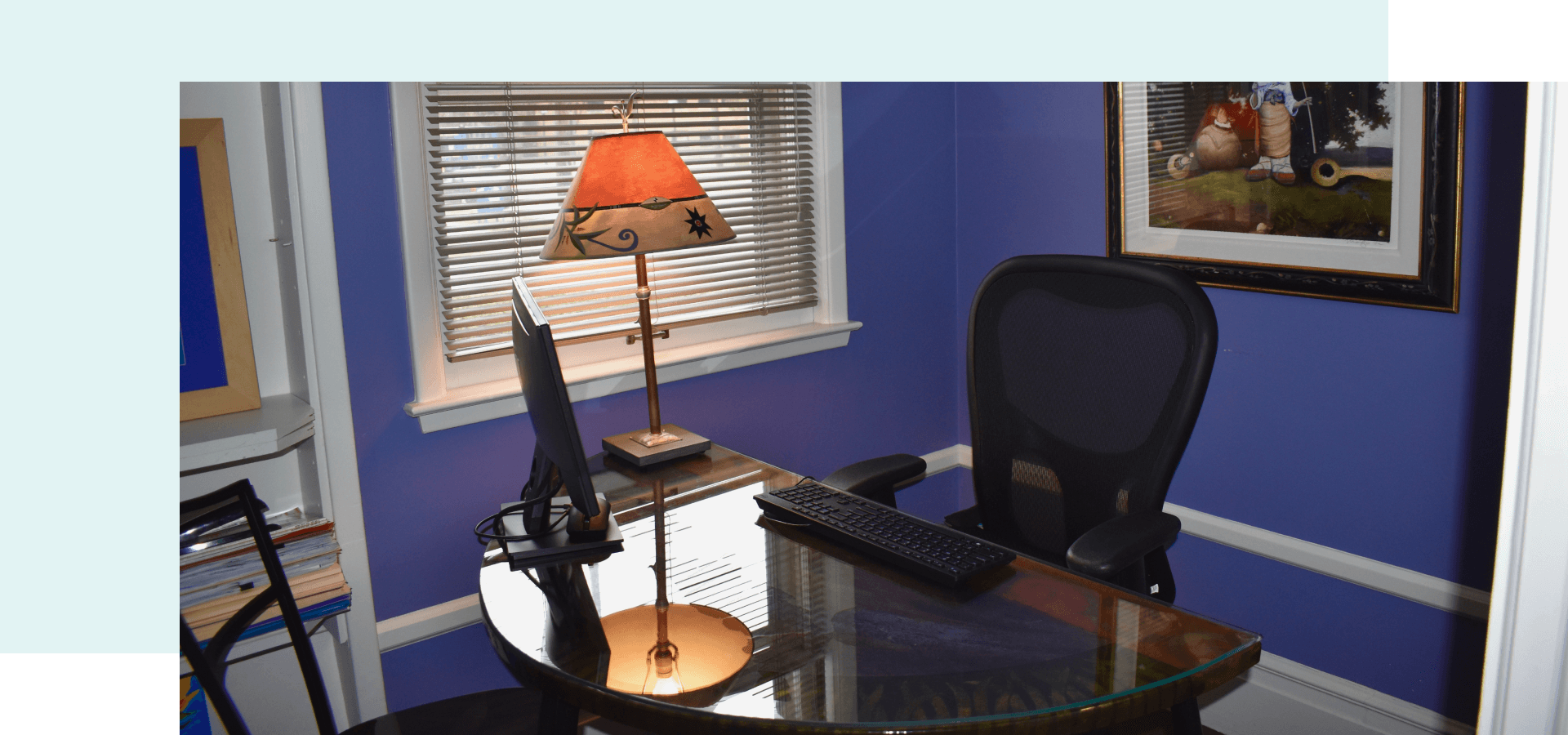 An office with purple walls and a desk, chair and computer