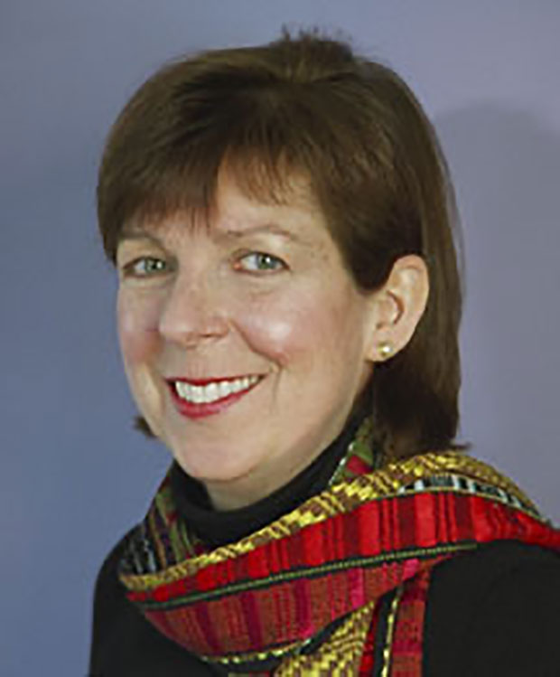 A head shot of a middle aged woman with short hair and wearing a red scarf